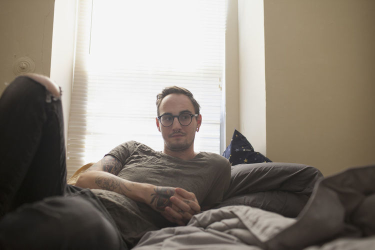 Full length of man sitting on bed at home