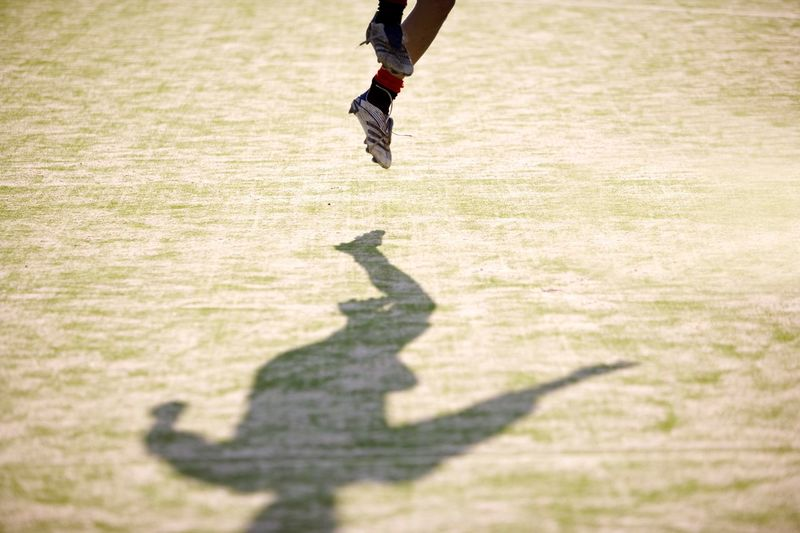 Low section of soccer player jumping over field on sunny day