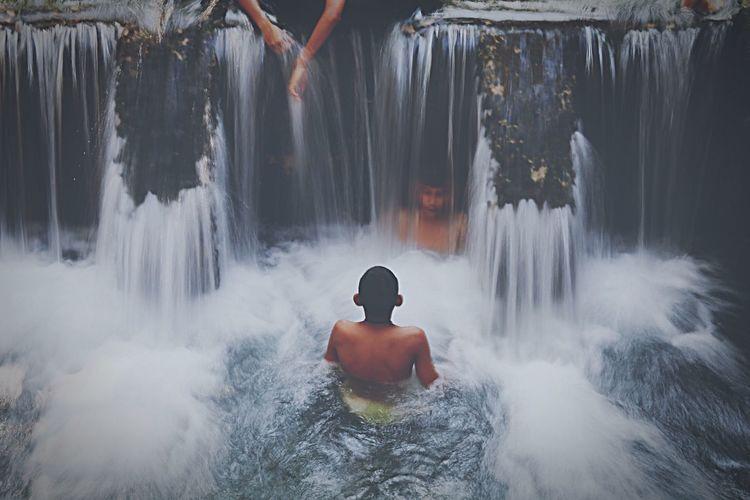 Shirtless men enjoying at waterfall