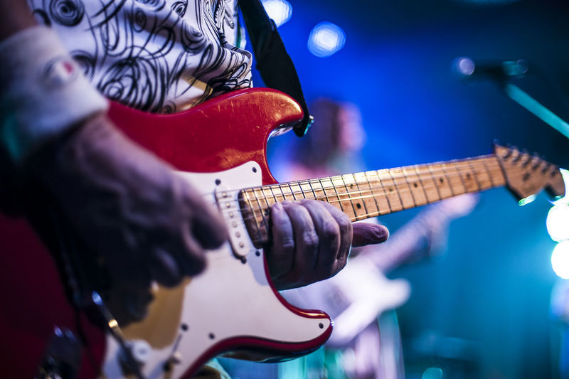 Midsection Of Guitarist Performing At Concert