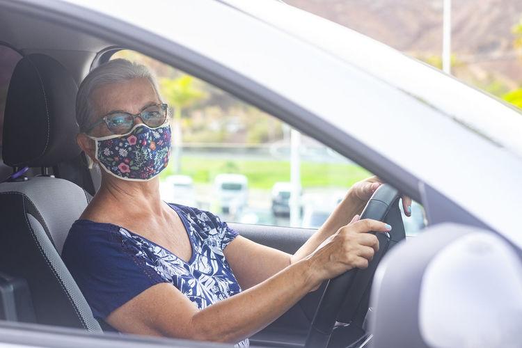 Portrait of smiling senior woman wearing flu mask sitting in car