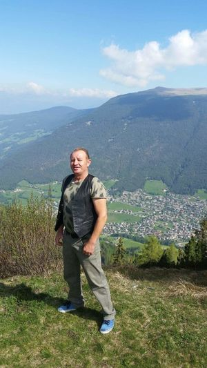 Portrait of mature man standing on mountain against sky