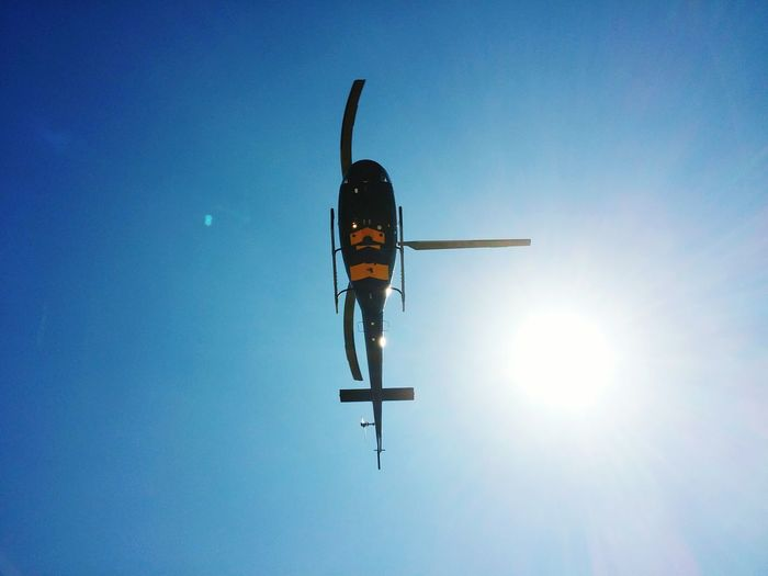 Directly below shot of helicopter flying against sky