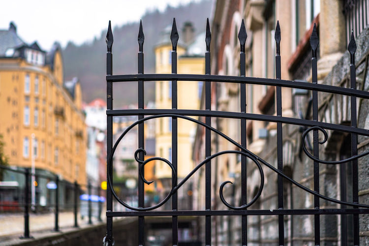Close-up of railing against buildings in city