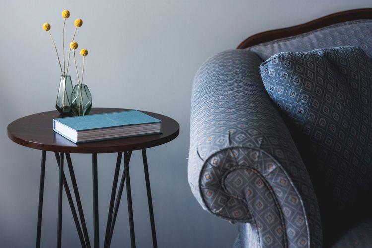 Close-up of book and flower vases on side table by sofa in living room