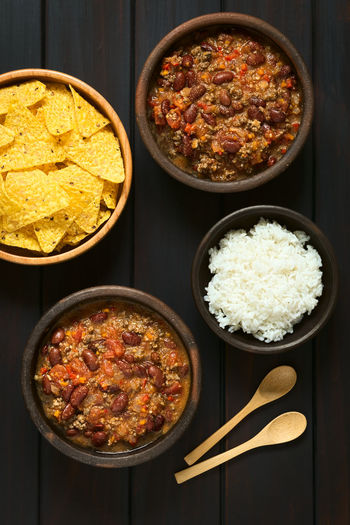 Chili con carne with rice and tortilla chips, photographed overhead on dark wood with natural light Beef Chili Con Carne Chilli Con Carne Dish Homemade Homemade Food Meal Rice Bean Carne Chili  Chilli Chips Cooked Food Food And Drink Fresh Ground Kidney Beans Meat Mincemeat Sauce Stew Tomato Tortilla Chips