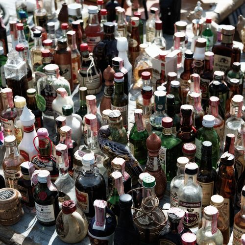 High angle view of alcohol bottles at flea market for sale