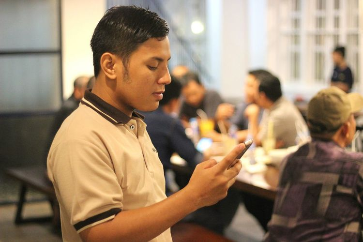 Side view of young man using smart phone while standing in restaurant