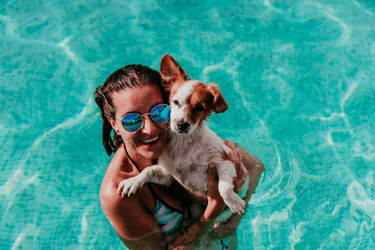 Young man with dog in swimming pool