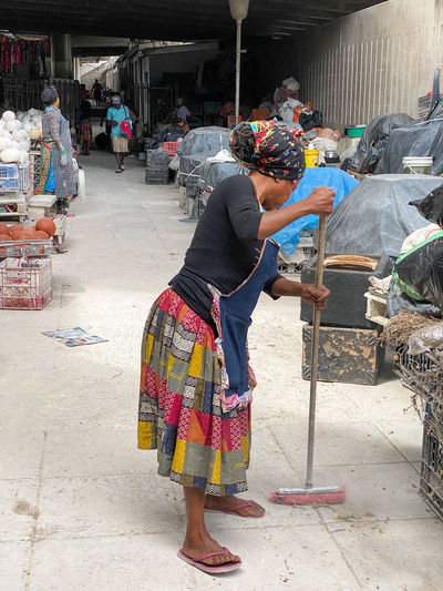Rear view of people working at market