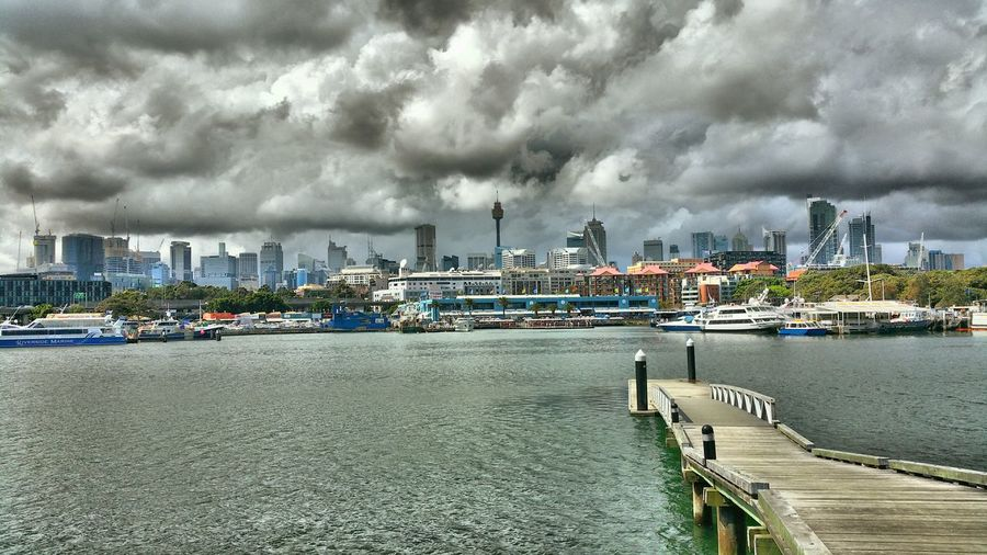 Boats at harbor against cloudy sky