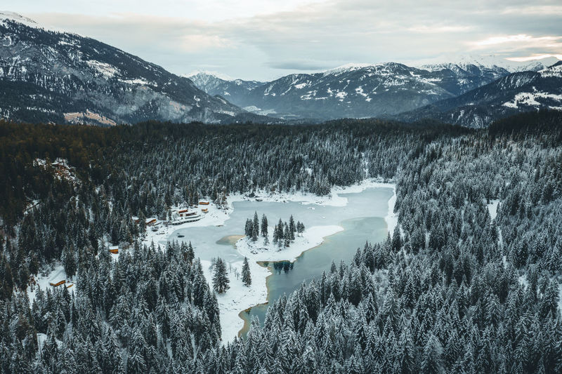half frozen lake and snow covered trees in Switzerland Mountain Scenics - Nature Snow Beauty In Nature Cold Temperature Winter Mountain Range Tranquil Scene Tranquility Nature Water Cloud - Sky Non-urban Scene Landscape No People Mountain Peak Snowcapped Mountain Outdoors Lake Frozen Frozen Lake Sunrise Forest Snow Covered Cabin