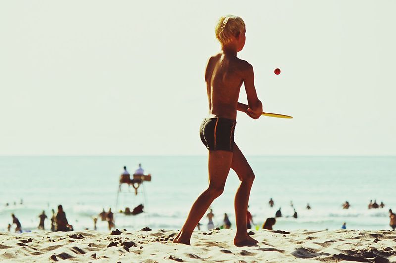 Teenage Boy Playing On Beach Against Clear Sky