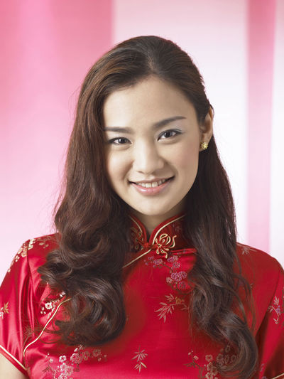 chinese woman wearing red cheongsam Red Happiness Laughing Tradition Traditional Clothing Woman Cheerful Chinese Chinese New Year Cultural Festival Front View Gong Xi Fa Chai Happiness Lifestyles Long Hair Looking At Camera Oriental Style Portrait Qipao Real People Smile Studio Shot Traditional Costume Wearing