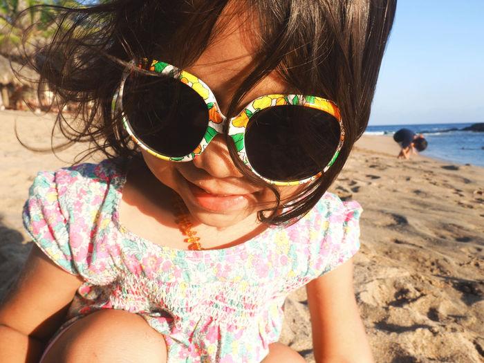 Close-Up Of Girl Wearing Sunglasses At Beach