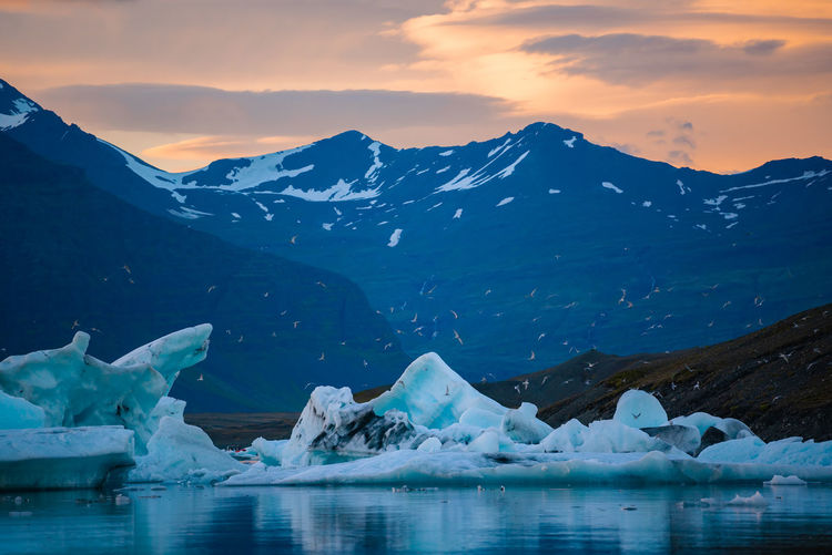Scenic view of icebergs on lake against sky during sunset