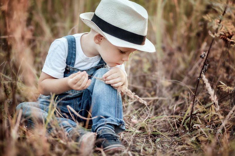 Cute boy sitting on field amidst plants