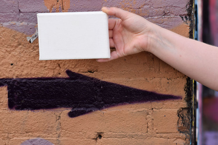 Woman's hand with a tiny canvas in front of an urban background Advertise Canvas Tiny Woman Advertisement Background, City, Design, Dirty, Display Flyer Grungy, Hand, Message Urban