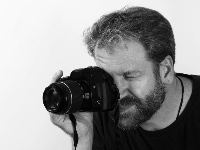 Portrait of man photographing against white background