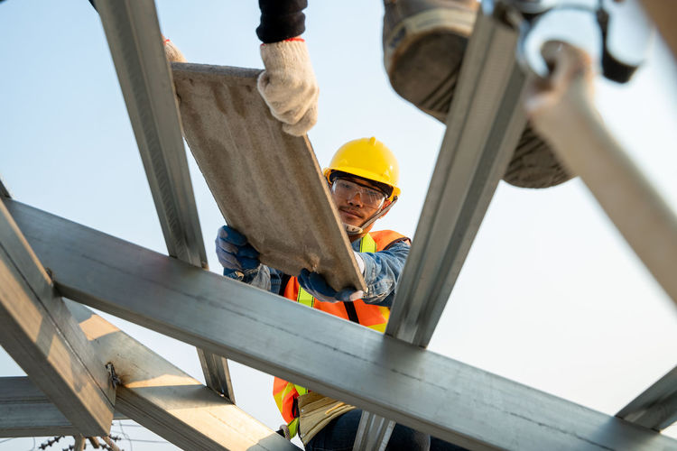 Low angle view of men working at construction site