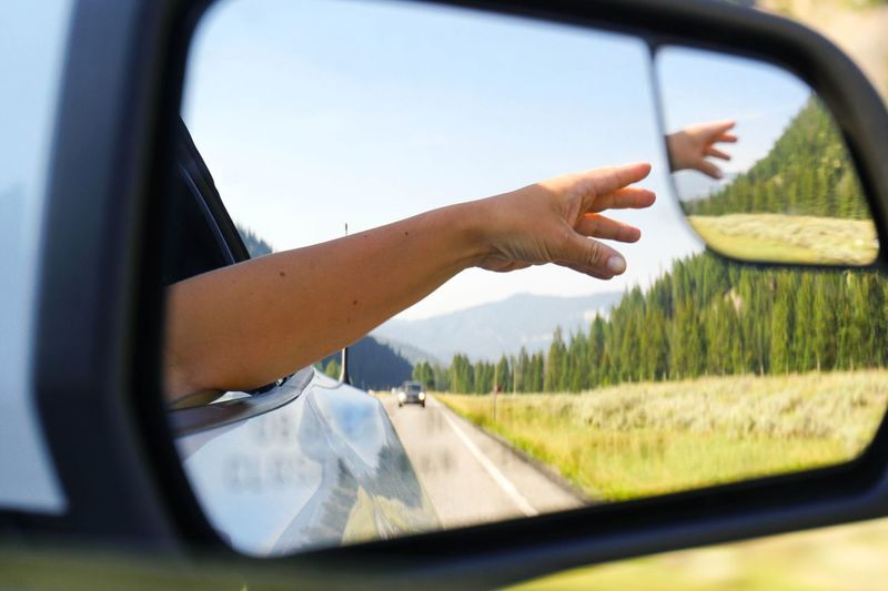 Hand Reflecting On Side-View Mirror Of Car