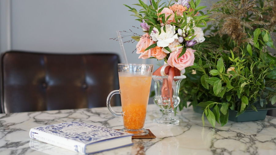 Close-up of drink by bouquet on marble table
