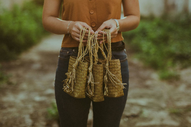 Midsection of woman holding wicker bags while standing outdoors