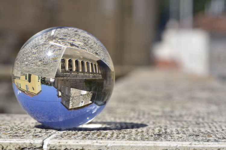 Close-up of crystal ball on metal in city