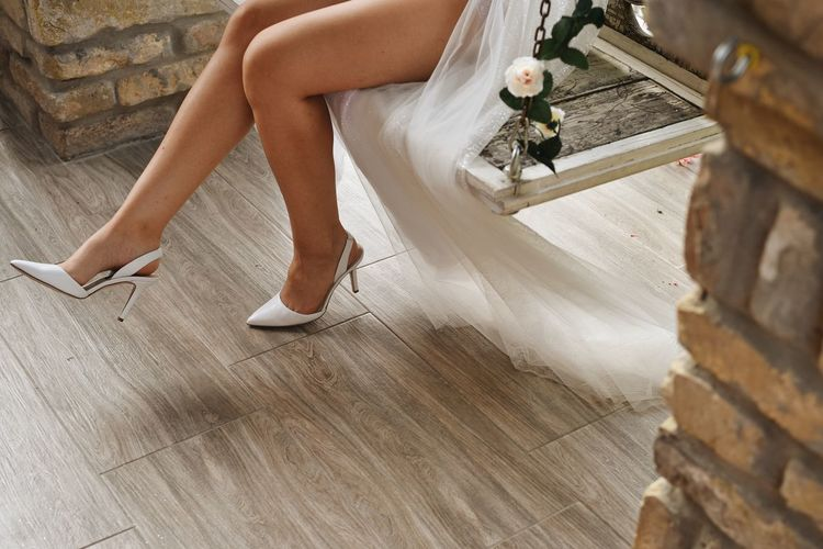 Low section of woman sitting on wooden floor