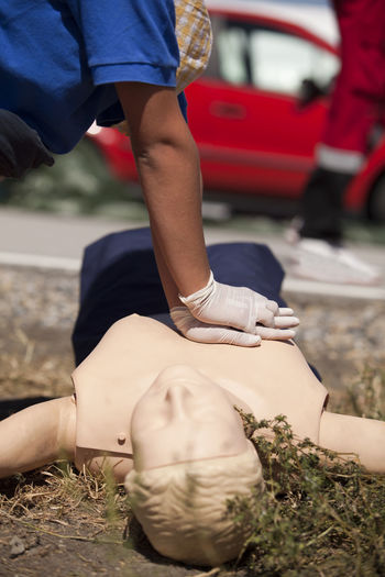 Midsection Of Man Practicing Cpr On Dummy On Field