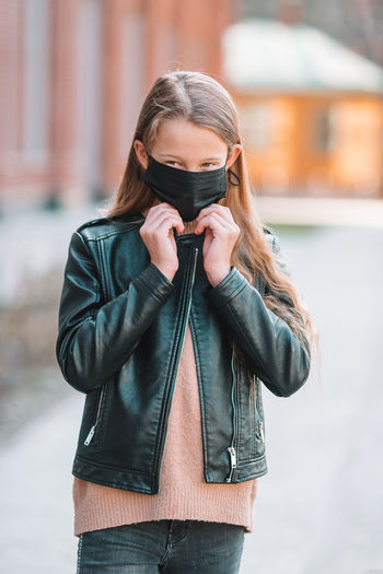 Girl wearing mask while standing outdoors