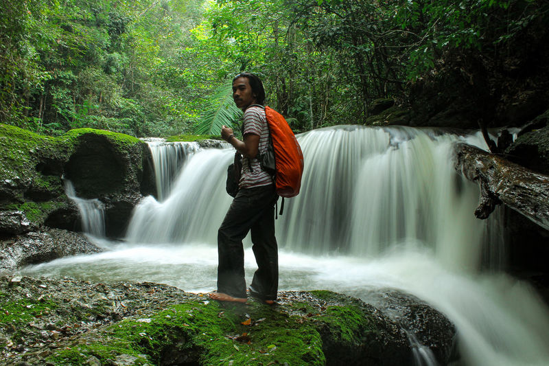 Full length of waterfall in forest
