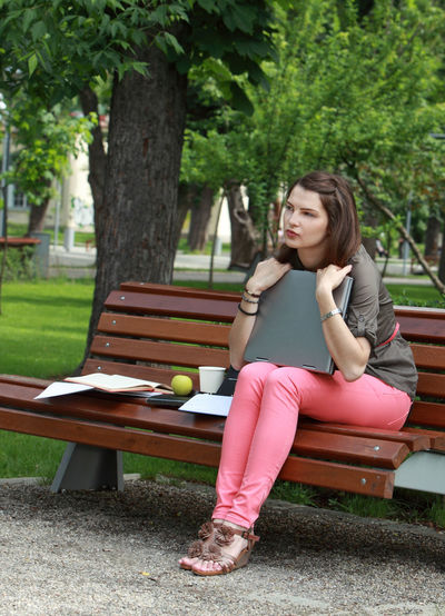 Young woman with a laptop on a bench in an urban park. Sitting One Person Young Adult Bench Leisure Activity Casual Clothing Park Nature Lifestyles Park - Man Made Space Contemplation Outdoors Park Bench Young Woman Technology Computer Woman Woman Portrait Alone