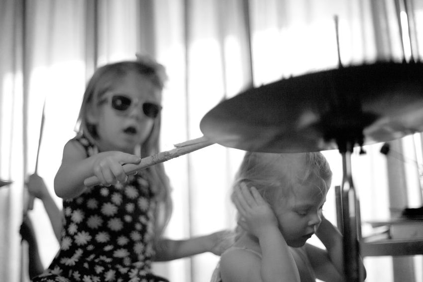 A young girl hits the cymbal on a drum set while her sister covers her ears because it is too loud. Cool Cymbal Cymbal Crash Domestic Life Drum Drums Ears Hearing Hi-hat Indoors  Loud Real People Siblings Sunglasses Two People