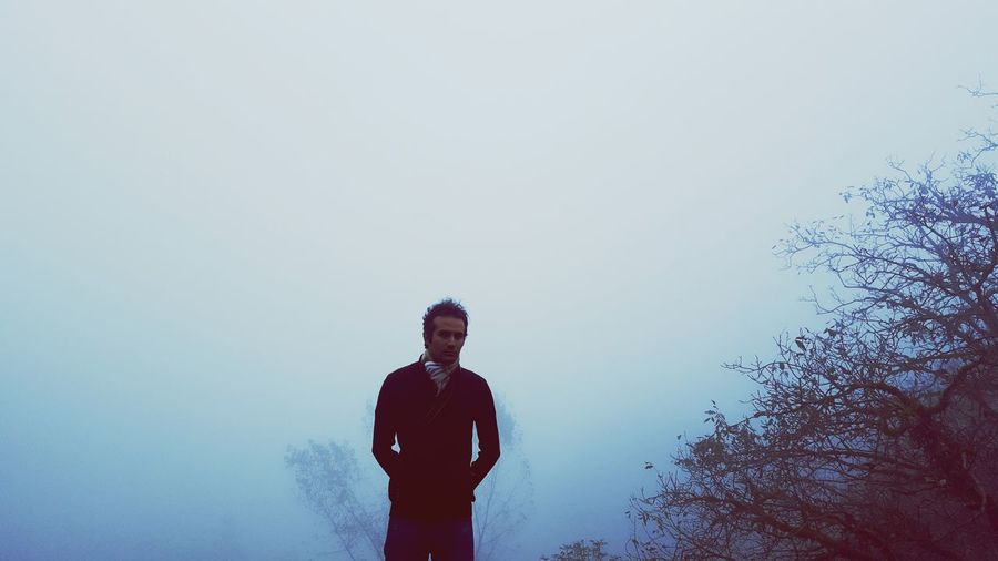 Man standing by bare tree during foggy weather