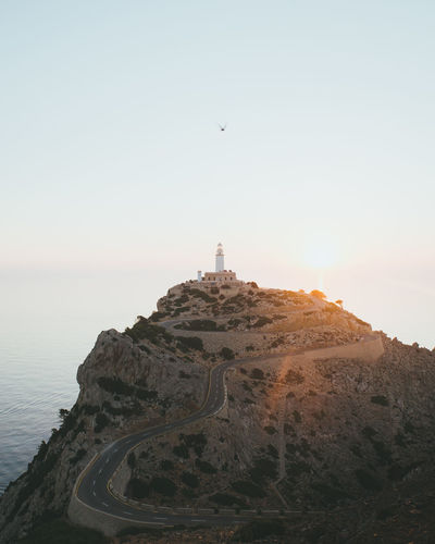 Lighthouse On Mountain Against Sea During Sunset