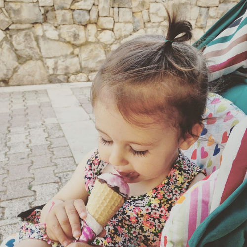 Close-Up Of Cute Girl Licking Ice Cream Against Stone Wall