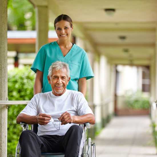 Smiling nurse assisting senior man at hospital