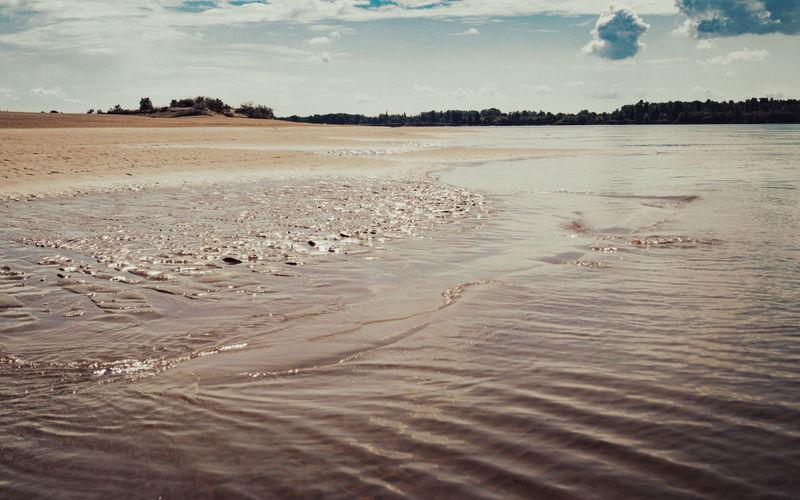 Surface level of wet sand on beach against sky