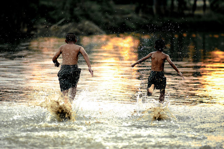 Two Asian boys friends running in the water in summer sunny of and freedom concept. ASIA Asian  Freedom Lifestyle Running Thai Activity Challenge Challenging Competition Friend Friendship Fun Motion Nature Playful River Running Schoolboy Splashing Sport Thaland Two People Water Wet