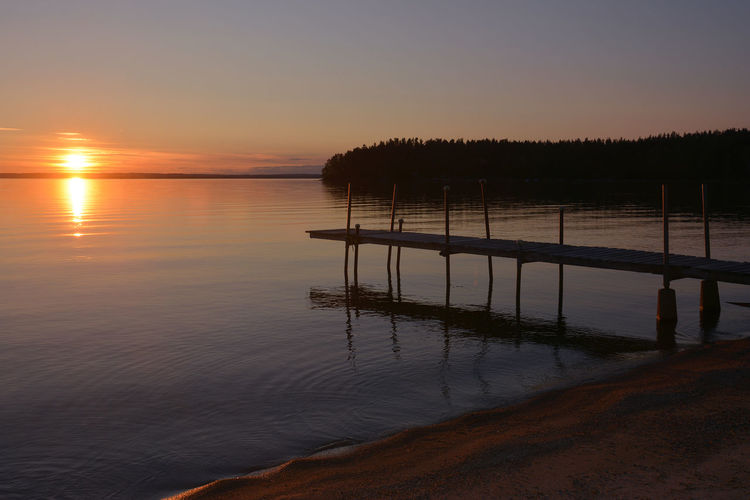 Wooden pier at sunset Peace And Quiet Pier Sweden Beauty In Nature Calm Water Evening Idyllic Jetty Lake Lake Vättern Landscape Nature No People Outdoors Peaceful Reflection Scenics Silence Silhouette Sky Sunset Tranquil Scene Tranquility Water Windless