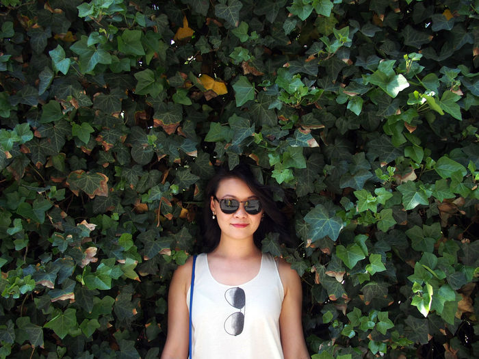 Portrait of young woman wearing sunglasses standing by plants