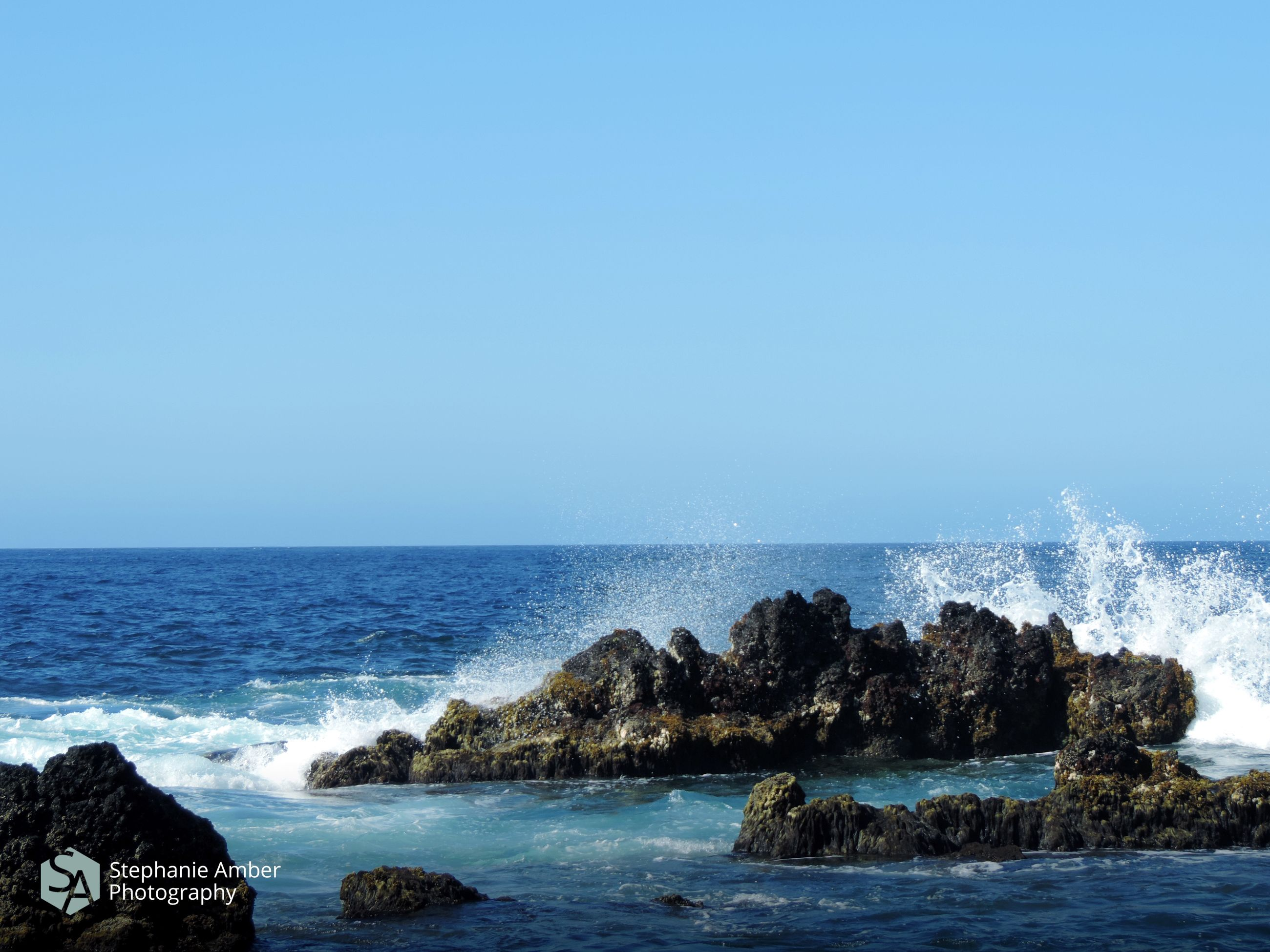 sea, water, horizon over water, sky, horizon, beauty in nature, clear sky, scenics - nature, rock, wave, copy space, rock - object, nature, splashing, blue, day, motion, no people, solid, power in nature, outdoors, breaking, hitting
