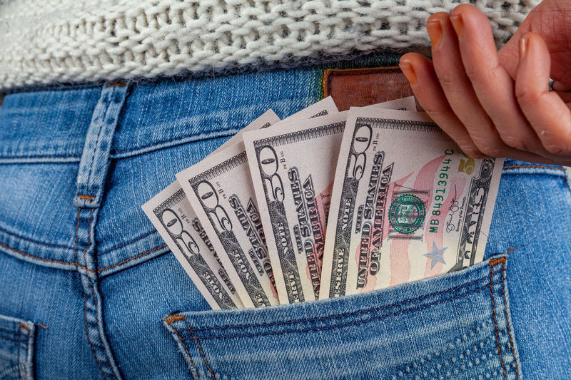 Midsection of woman putting us currency in pocket