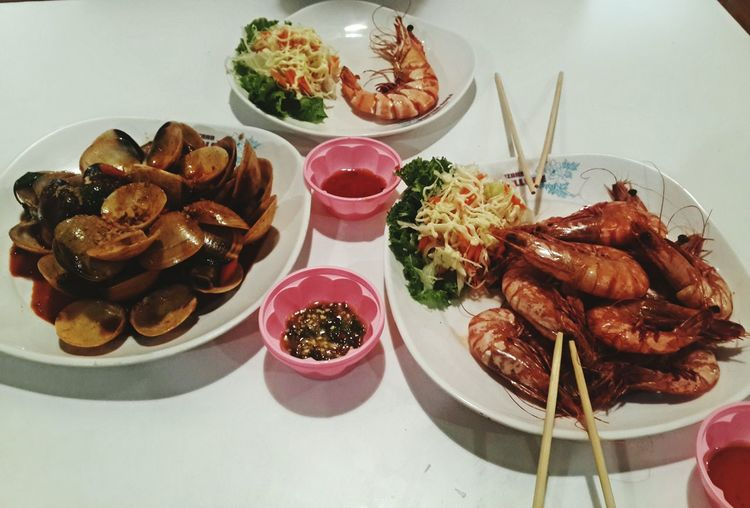 High angle view of seafood served in plates on table