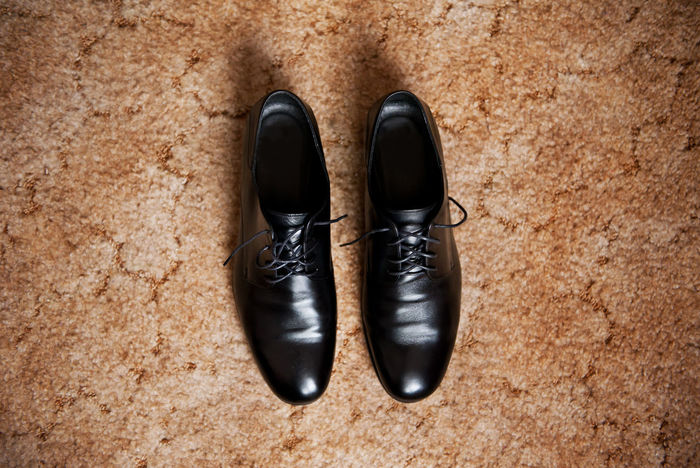 Male dress shoes, elegance wedding groom boots called derby shoes, leather black cloth empty shoes on beige carpet in horizontal orientation, nobody. Black Black Color Boot Boots Bridal Bridegroom Carpet Derby Directly Above Elegance And Class Footgear Footwear Footwears Groom Leather Pair Shoe Two Wedding