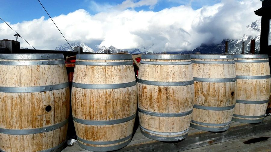 Close-up of wine casks against cloudy sky