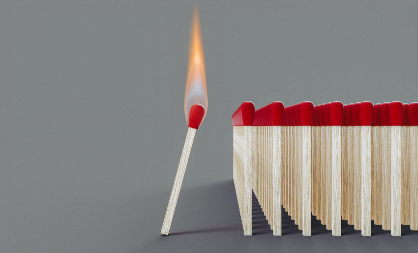 Close-up of lit candle against white background