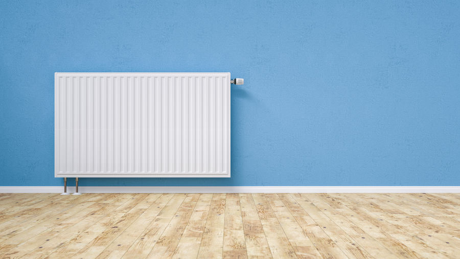 Radiator on blue wall at home