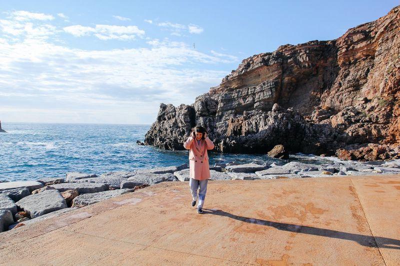 Woman walking on promenade against rocky cliff